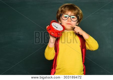 Kids Gets Ready For School. Cute Little Boy Turns Off Alarm Clock Waking Up In The Morning From A Ca