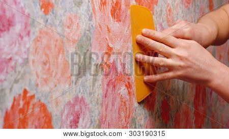 Contractor Repairing Apartment. Close Up Hand Of Decorator Smoothing Wallpaper Using Spatula. Home R
