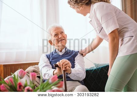 Senior Man With A Walking Stick Being Comforted By Nurse In The Hospice