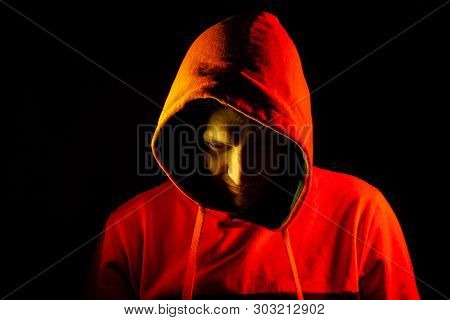An Adult Man Looks Out From Under The Hood With A Grin Like A Psycho Or A Maniac In An Orange Hooded