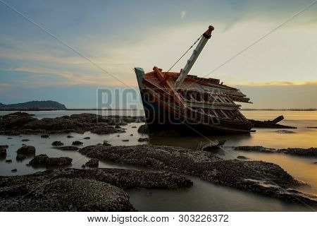 Shipwreck With Rocks During Sunset. Shipwreck On Beach.