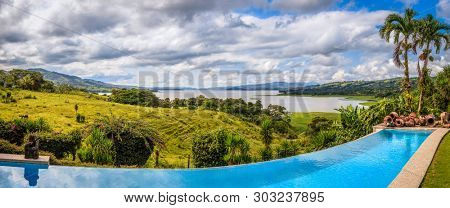 Scenic panoramic view of Lake Arenal from a resort with infinity pool