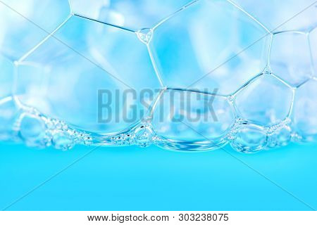 Foam. Soap foam popping bubbles background. Soap sud macro structure. Soap foam close-up, blue background poster