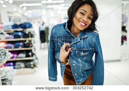 Chic African American Woman In Brown Tunic Dress And Jeans Jacket Posed At Clothes Store. It's Time