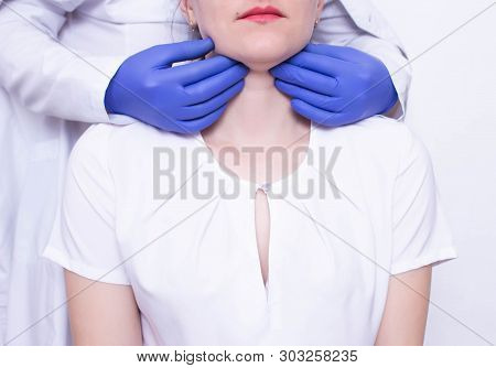 Doctor Specialist Diagnoses Palpation On The Throat Of The Caucasian Girl For The Presence Of Enlarg