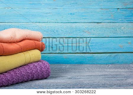 Knitted wool sweaters. Pile of knitted summer clothes on wooden background, sweaters, knitwear, space for text. poster