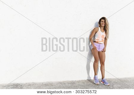 Attractive Joyful Athletic Female Fitness Instructor Leaning White Concrete Wall Outside, Smiling Ca