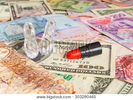 Glass Pair Of Shoes And Red Lipstick On Banknotes Of Different Countries. Money For Love. Prostituti