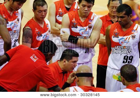 KUALA LUMPUR - FEB 19: Malaysian Dragons coach Ariel Vanguardia (seated) stresses a point during time-out at the ASEAN Basketball League game against Singapore Slingers on Feb 19, 2012 in Kuala Lumpur, Malaysia.