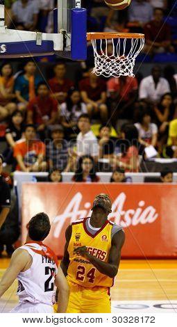 KUALA LUMPUR - FEBRUARY 19: Slingers L. Graham (24) and Dragons Ernani Pacana's (22) watch the ball at an ASEAN Basketball League match on February 19, 2012 in Kuala Lumpur, Malaysia.  Dragons won 86-71.
