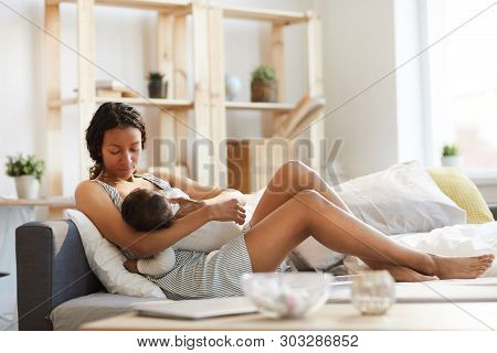 Serious Calm Careful Young Black Mom Sitting On Sofa Bed And Breastfeeding Baby While Holding Son In