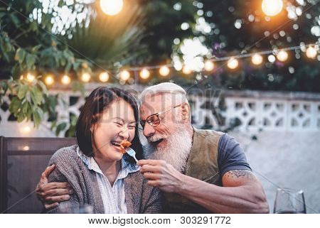 Happy Senior Couple Having Fun At Dinner House Party - Older People With Different Ethnicity Doing A