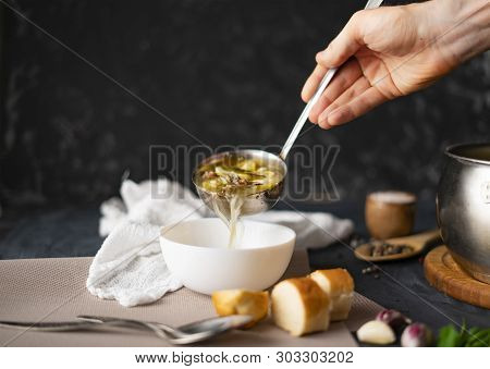 Chefs Hand Pour Fresh Hot Soup In A White Empty Bowl, Food Preparations
