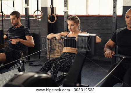 Young man and beautiful woman working out with rowing machine at crossfit gym. Athletic class doing exercise with rowing machine. Group of fitness concentrated people in sportswear training.