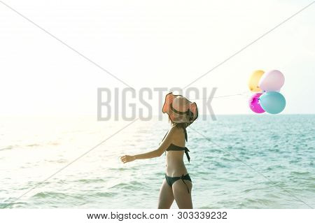 Woman In Bikini Swin Suit Is Taking Colouful Balloon And Walking On The Beach As For Summer Vacation