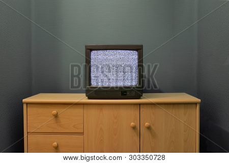 No signal just noise on old analogue TV set in a dim room