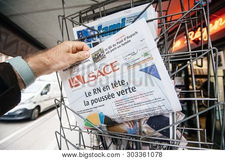Strasbourg, France - May 27, 2019: Man Holding Buying Lalsace Newspaper Front Page On Street Press K