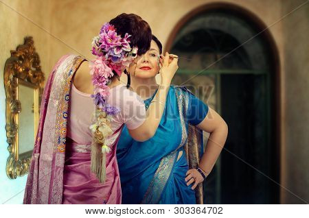 Two Women Dancers In A Sari. One Dancer In Pink Sari Turns Back To Apply Makeup On The Face Of Anoth
