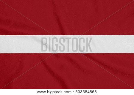 Flag Of Latvia On Textured Fabric. Patriotic Symbol
