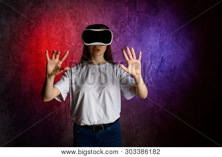 Young Woman Touching The Air During The Vr Experience. Blue And Red Background
