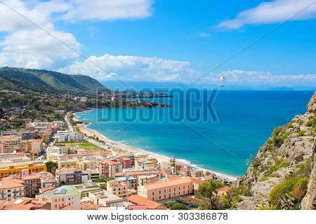 Paraglider Flying Above The Amazing Landscape Of Coastal City Cefalu In Beautiful Sicily. Paraglidin