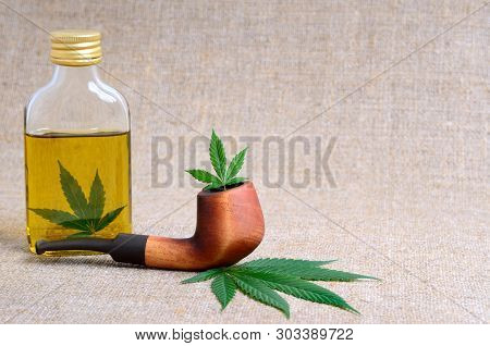 Marijuana, Smoking Pipe And Hemp Oil In A Transparent Bottle. Cannabis Extract, Medicine And Food Su
