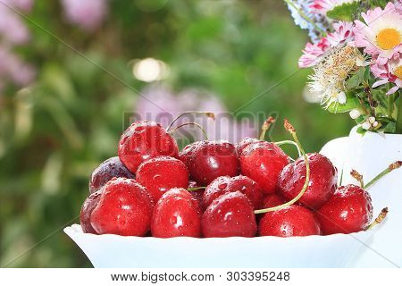A Cup Of Cherries On A Sunny Table In A Flowered Garden, Selective Focus. Sweet Cherry With Droplets