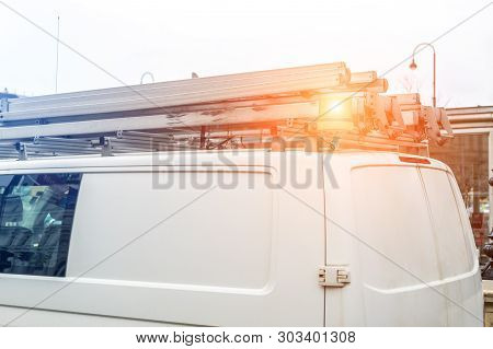 White Repair And Service Van With Ladder And Orange Light Bar On Roof At City Street. Assistance Or