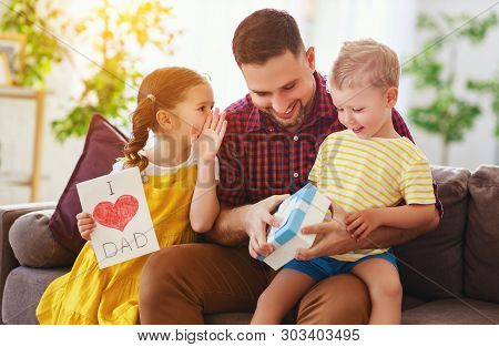Happy Father's Day! Children Congratulates Dad And Gives Him Gift And Postcard
