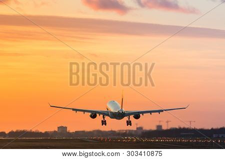 Airplane Is Landing At Airport During A Wonderful Evening Dramatic Sunset Sky Background / Wide-body