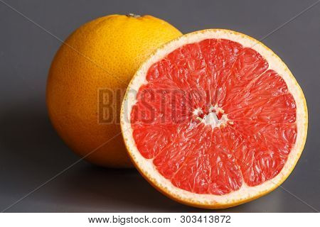 Half And Whole Grapefruits On Gray Background