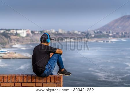 A Peruvian Guy Listening With His Earphone On At Beach Of Lima,  Peru