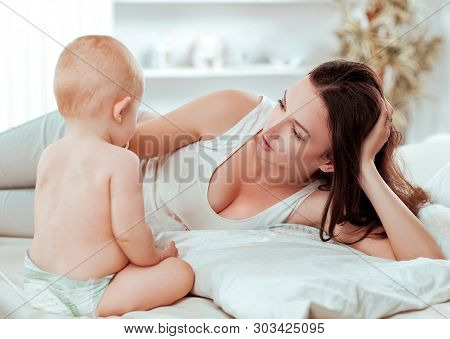 Happy Mom Talking To The Baby Lying On The Bed