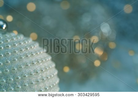 Christmas Decoration. Ball With Nacre Pearls And Beautiful Blurred Background Of Glittering Bokeh Wi