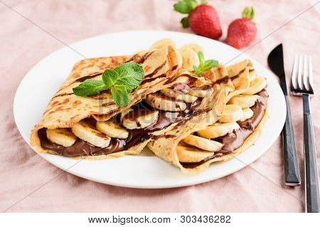 Crepe With Chocolate Spread And Banana On White Plate On Pink Background. Tasty Dessert