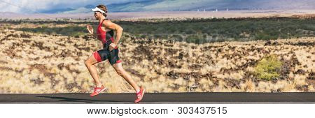 Triathlon runner triathlete man running in tri suit at ironman competition race. Panorama banner. Sport athlete on marathon run training in professional tri outfit for triathlon. Fitness in Hawaii.