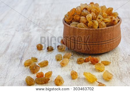 Light Yellow Raisins In A Wooden Bowl On A Light White Background. Close-up. Isolated.
