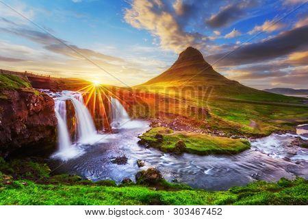 Morning landscape with rising sun on Kirkjufellsfoss waterfall and Kirkjufell mountain, Iceland, Europe.