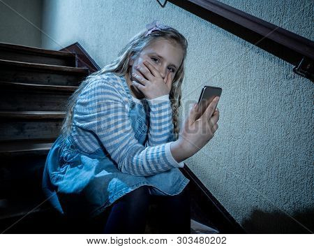 Sad Depressed Unhappy Child Suffering From Cyberbullying By Mobile Smart Phone Sitting Alone.