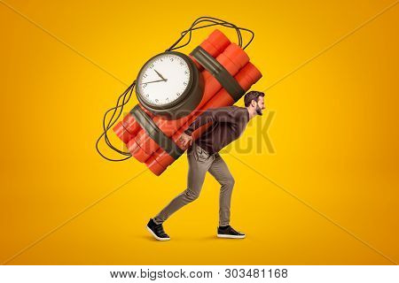Young Man In Casual Clothes Carrying Big Red Dynamite Stick Time Bomb On His Back On Yellow Backgrou