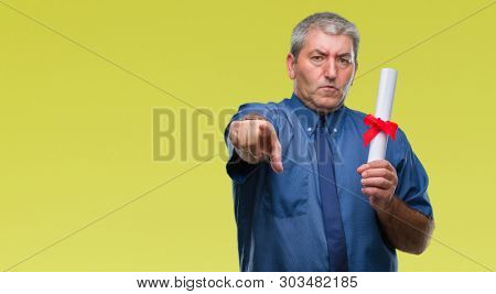 Handsome senior man holding degree over isolated background pointing with finger to the camera and to you, hand sign, positive and confident gesture from the front