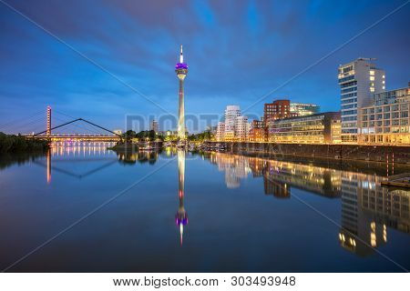 poster of Dusseldorf, Germany. Cityscape image of DÑŒsseldorf, Germany with the Media Harbour and reflection of the city in the Rhine river, during twilight blue hour.
