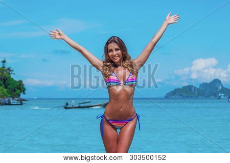 Portrait of young model woman in bikini raising her arms at tropical beach in Thailand