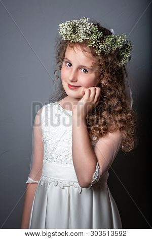 First Holy Communion. Caucasian Girl Wearing First Holy Communion Dress. Girl Preparing To Take Firs