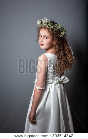 Caucasian Girl Wearing First Holy Communion Dress. Girl Preparing To Take First Communion. First Com
