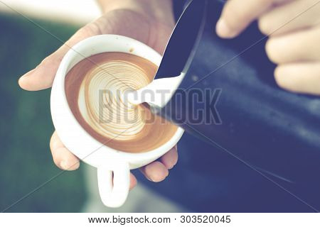 Closeup Image Of Male Barista Holding And Pouring Milk For Prepare Cup Of Coffee, Latte Art, Vintage
