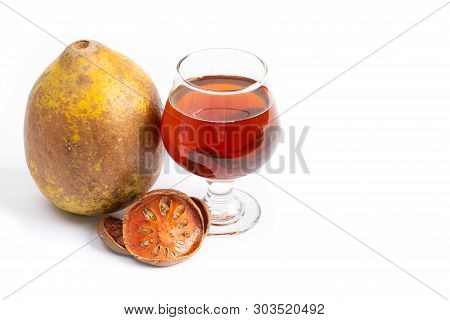 Bael Fruit Tea - A Glass Of Bael Fruit Tea And Dried Fruit Bale Beverage On A White Background