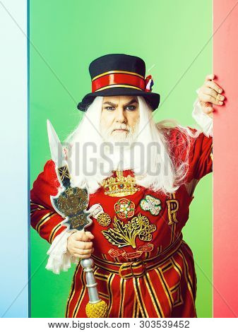 Frown Senior Man Beefeater Yeomen Warder Or Male Royal Guard Bodyguard In Red Uniform With Spear On