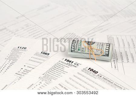 Tax Forms Lies Near Roll Of Hundred Dollar Bills. Income Tax Return