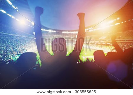 Happy football fans support their team and celebrating goal with hands up. Big stadium